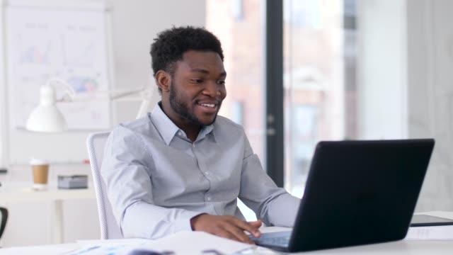 vídeos de stock e filmes b-roll de businessman having video chat on laptop at office - gesticular