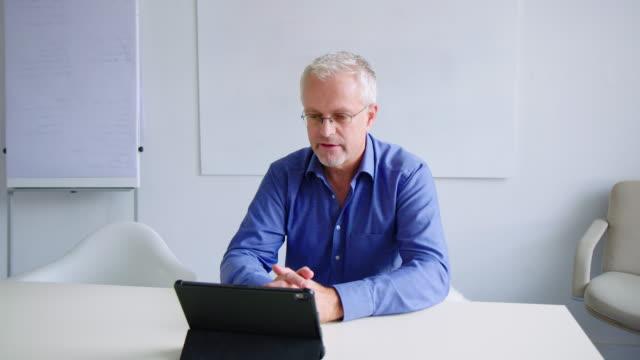 デジタルタブレットでビデオ会議を開くビジネスマン ビデオ