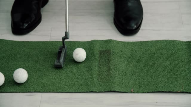 Businessman hits a golf shot towards the putting green