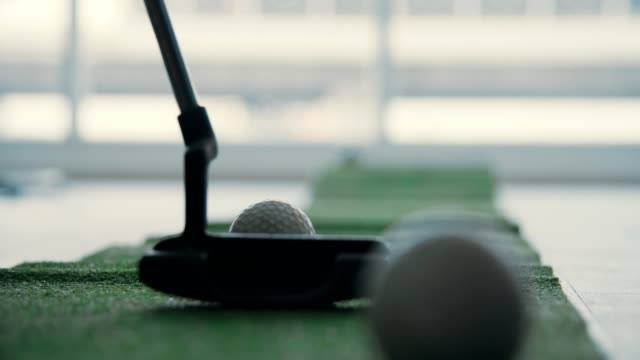 Businessman hitting a golf shot towards the putting green at office