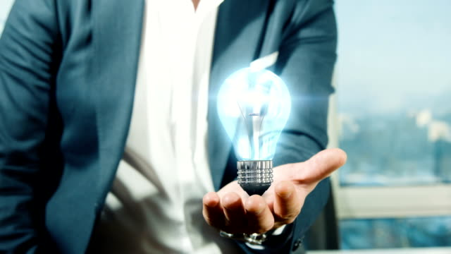 businessman holding light bulb | idea - idea stock videos & royalty-free footage