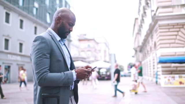 businessman holding mobile phone and standing on city street - dolly shot video stock e b–roll
