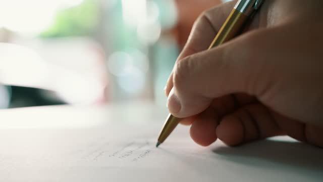 vídeos de stock, filmes e b-roll de empresário segurando caneta escrevendo em papel para novas informações de compromissos no conceito organizador - escrever