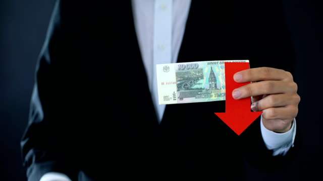 Businessman holding russian ruble banknotes showing thumbs up and down, falling