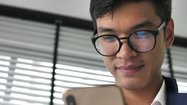 スマートフォンを持ち、オフィスを見ているビジネスマン ビデオ