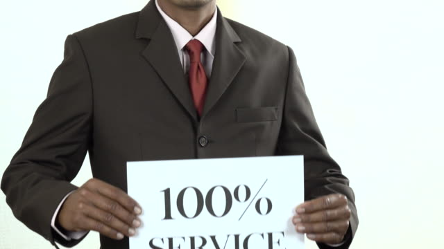 Businessman holding white card with 100% Service sign