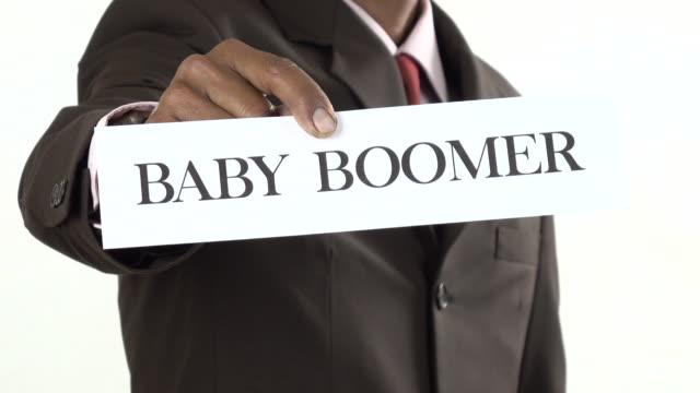Businessman holding white card with Baby Boomer, Gen X, Gen Y, Gen Z sign