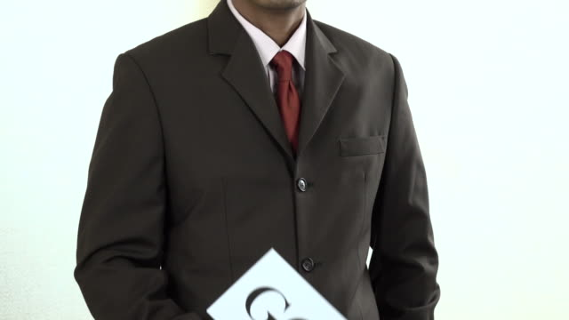 Businessman holding white card with Goals sign
