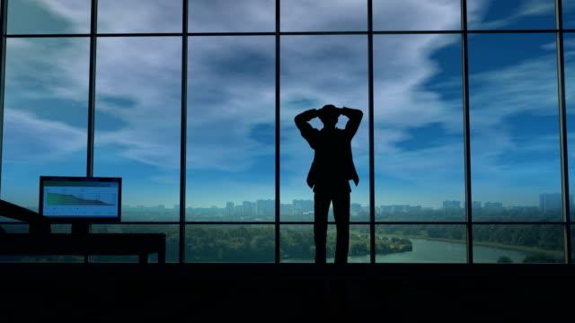 一位商人持有他的頭在他的辦公室時雷雲圍在他身邊 - 危機 個影片檔及 b 捲影像