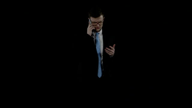 Businessman in a black suit stands and talks on a mobile phoner over black screen video