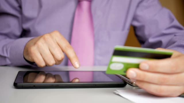 A businessman in a purple shirt and tie is making a payment to internet banking. Shopping online with credit card on digital tablet.