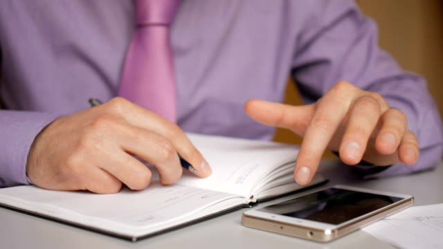 Businessman in a purple shirt and tie makes notes in a notebook. Man writes a pen in daily. A person makes notes in organizer. Laptop and smartphone on office desk in office. Closeup.