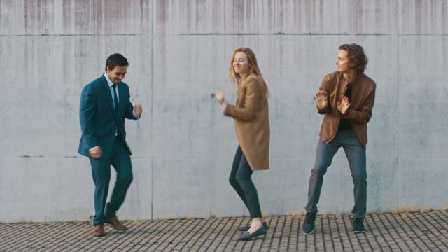 бизнесмен в костюме, веселая повседневная девушка и счастливый молодой хипстер танцуют на улице рядом с бетонной стеной. солнечный день. - элемент здания стоковые видео и кадры b-roll