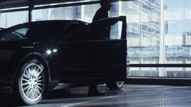 stockvideo's en b-roll-footage met zakenman in een pak krijgt uit een zwarte uitvoerende auto in een garage parkeerplaats. - parkeren