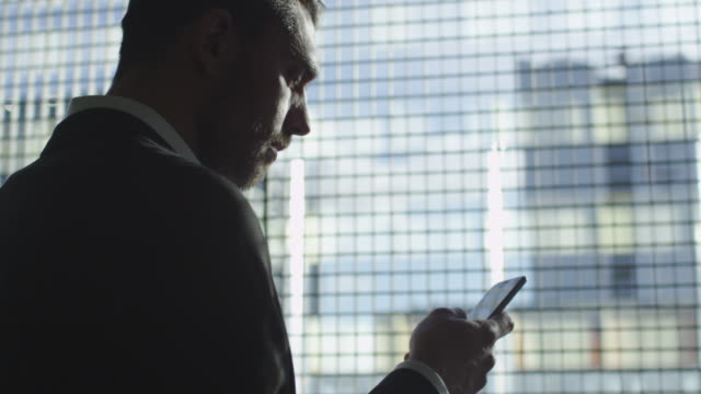 Businessman in a suit is using a smartphone next to a big window in a garage. video