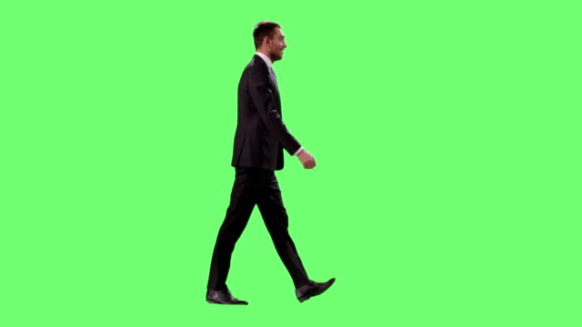 businessman in a suit is walking on a mock-up green screen in the background. - business suit stock videos & royalty-free footage