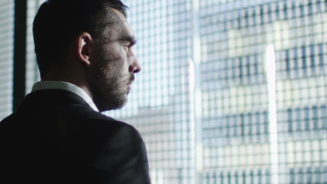 Businessman in a suit looks out of a big window in a city on a sunny day. video