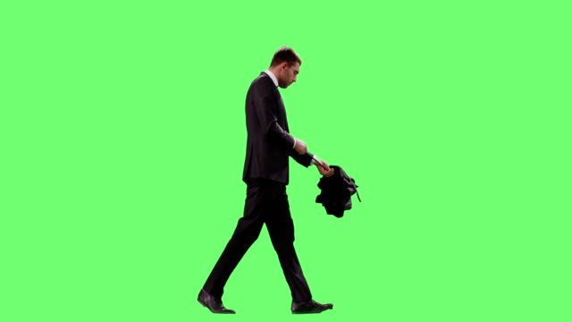 vídeos de stock e filmes b-roll de businessman in a suit opens umbrella while walking. shot on mock-up green screen. - homem chapéu