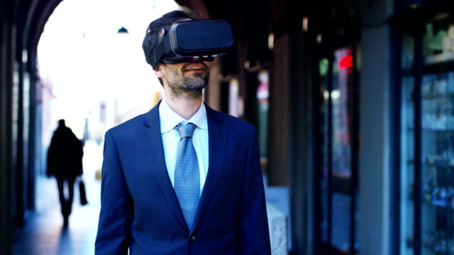 ein geschäftsmann in einem anzug nutzt augmented reality in der stadt unter den menschen. - editorial videos stock-videos und b-roll-filmmaterial