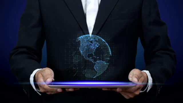 4K. businessman in black suit holding tablet computer with blue digital hologram of world revolves above on tablet screen