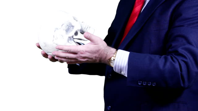 Businessman in blue suit with a human skull. video