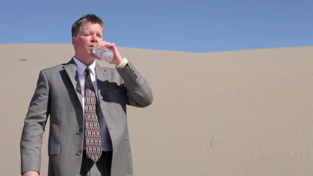 Businessman in desert drinking water video