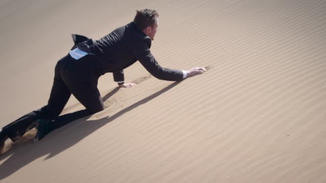 vidéos et rushes de homme d'affaires dans le désert - ramper