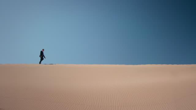vídeos de stock e filmes b-roll de empresário no deserto - linha do horizonte sobre terra