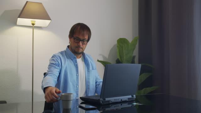 Zakenman in oogglazen met laptopcomputer die koffie of thee op bureau drinkt. Bedrijfs-, mensen- en technologieconcept video