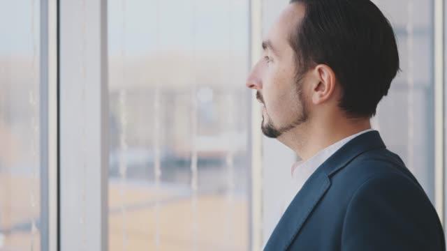 uomo d'affari in suite formale si trova di fronte alla finestra panoramica con vista sulla città. uomo sorridente. vista del profilo. profilo fuoribordo. da vicino. animazione. 4k. - dorso umano video stock e b–roll