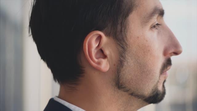 uomo d'affari in suite formale si trova di fronte alla finestra panoramica con vista sulla città. uomo serio. vista profilo. profilo fuoribordo. da vicino. animazione. 4k. - dorso umano video stock e b–roll