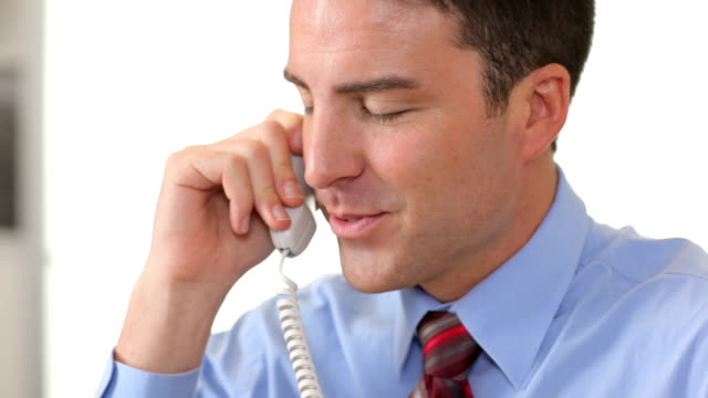 Businessman in office talking on telephone HD 1080p: Businessman in office talking on telephone telephone receiver stock videos & royalty-free footage