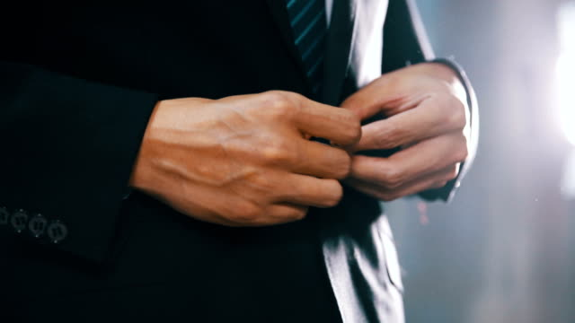 businessman in suit fastening button on jacket video