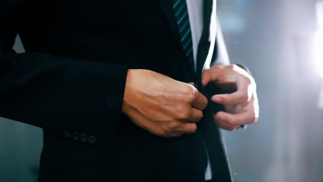 businessman in suit fastening button on jacket