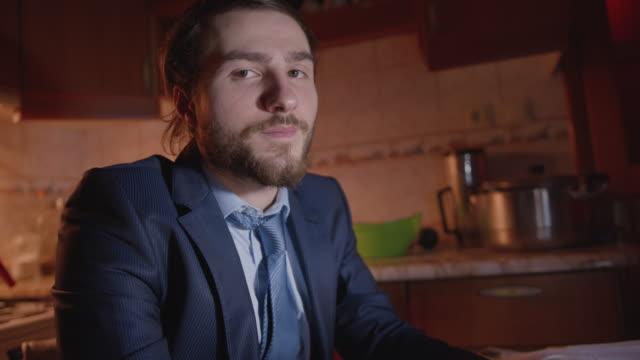 affärsman i kostym gör tummen upp bock medan du tittar in i kameran medan du arbetar på den bärbara datorn i köket. dolly-rörelsen. - thumbs up bildbanksvideor och videomaterial från bakom kulisserna