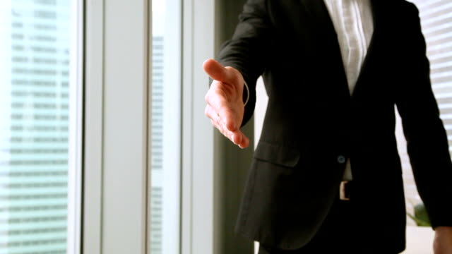 Businessman in suit reaching out hand offering handshake, close up video