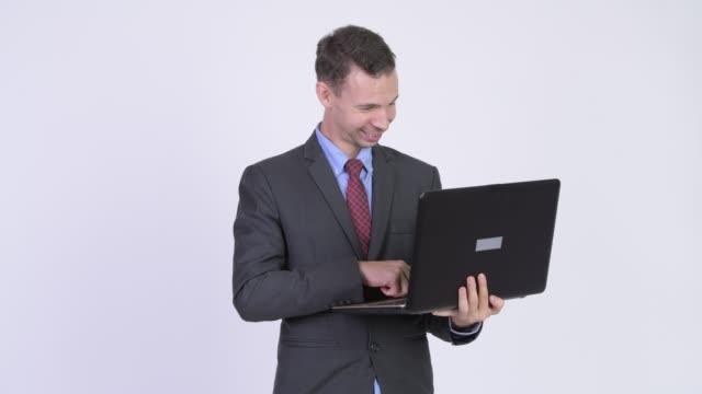 dizüstü bilgisayar kullanan iş adamı takım elbiseli - bir orta yetişkin erkek sadece stok videoları ve detay görüntü çekimi