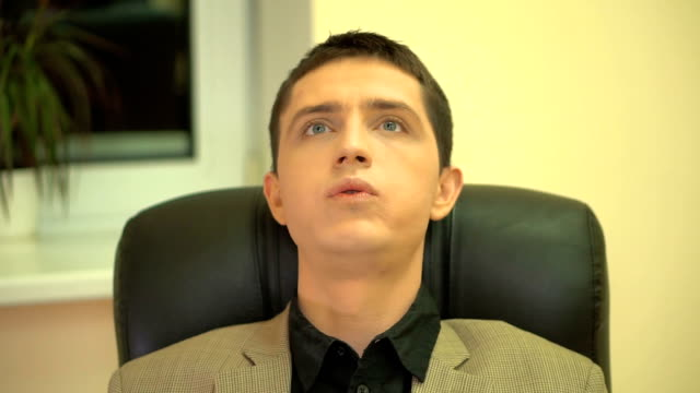 Businessman in the armchair sighed with relief and closes his eyes after a stressful day of work video