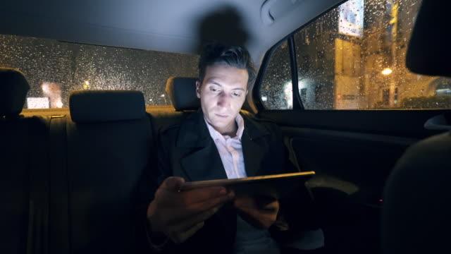 デジタル タブレットを使用して車の中で実業家。 ビデオ