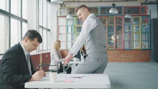 オフィスのビジネスマンは冗談を言い、同僚に歩み、テーブルに座り、書類を見て捨てる。部長の同僚は激怒している。トレンディなオフィスインテリア。コワーキング ビデオ
