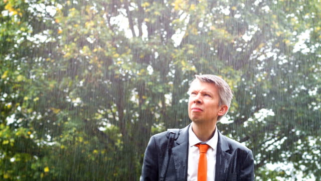 Businessman in the rain Sad businessman in the rain without an umbrella drenched stock videos & royalty-free footage