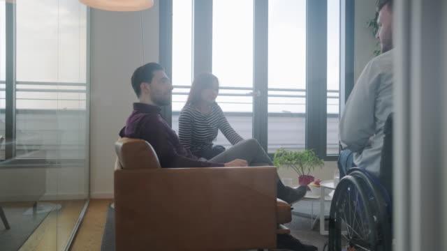 vídeos de stock e filmes b-roll de businessman in wheelchair sharing ideas with associates - envolvimento dos funcionários