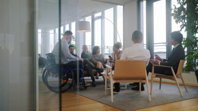 vídeos de stock e filmes b-roll de businessman in wheelchair talking with associates in lobby - pessoas com deficiência