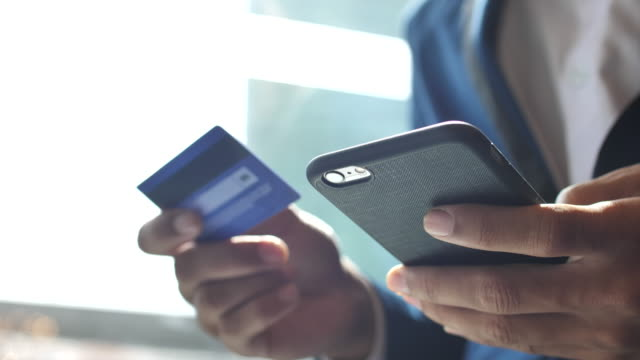 businessman inserting credit card number on mobile phone, slow motion - borsa della spesa video stock e b–roll