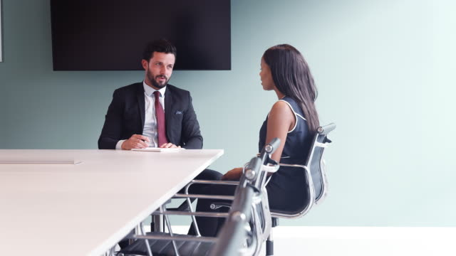 Businessman Interviewing Female Candidate At Graduate Recruitment Assessment Day In Office Businessman Interviewing Female Candidate At Graduate Recruitment Assessment Day In Office job interview stock videos & royalty-free footage