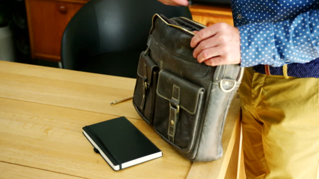 vídeos de stock e filmes b-roll de businessman is finishing work and packing his briefcase - mochila saco