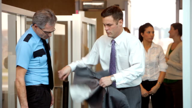 Businessman is inspected by airport security video