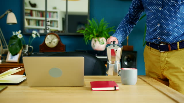 vídeos de stock e filmes b-roll de businessman is pouring  cup of coffee at his home office - hygge
