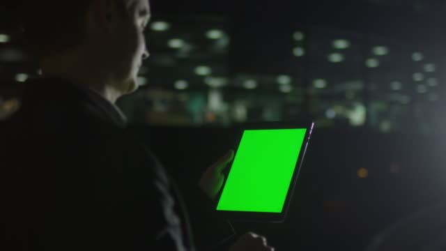 Businessman is Using Tablet With Green Screen at Night video