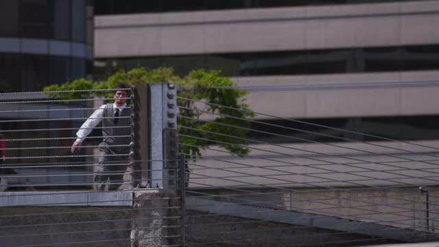 geschäftsmann springen über parkgarage barrier - stuntman stock-videos und b-roll-filmmaterial
